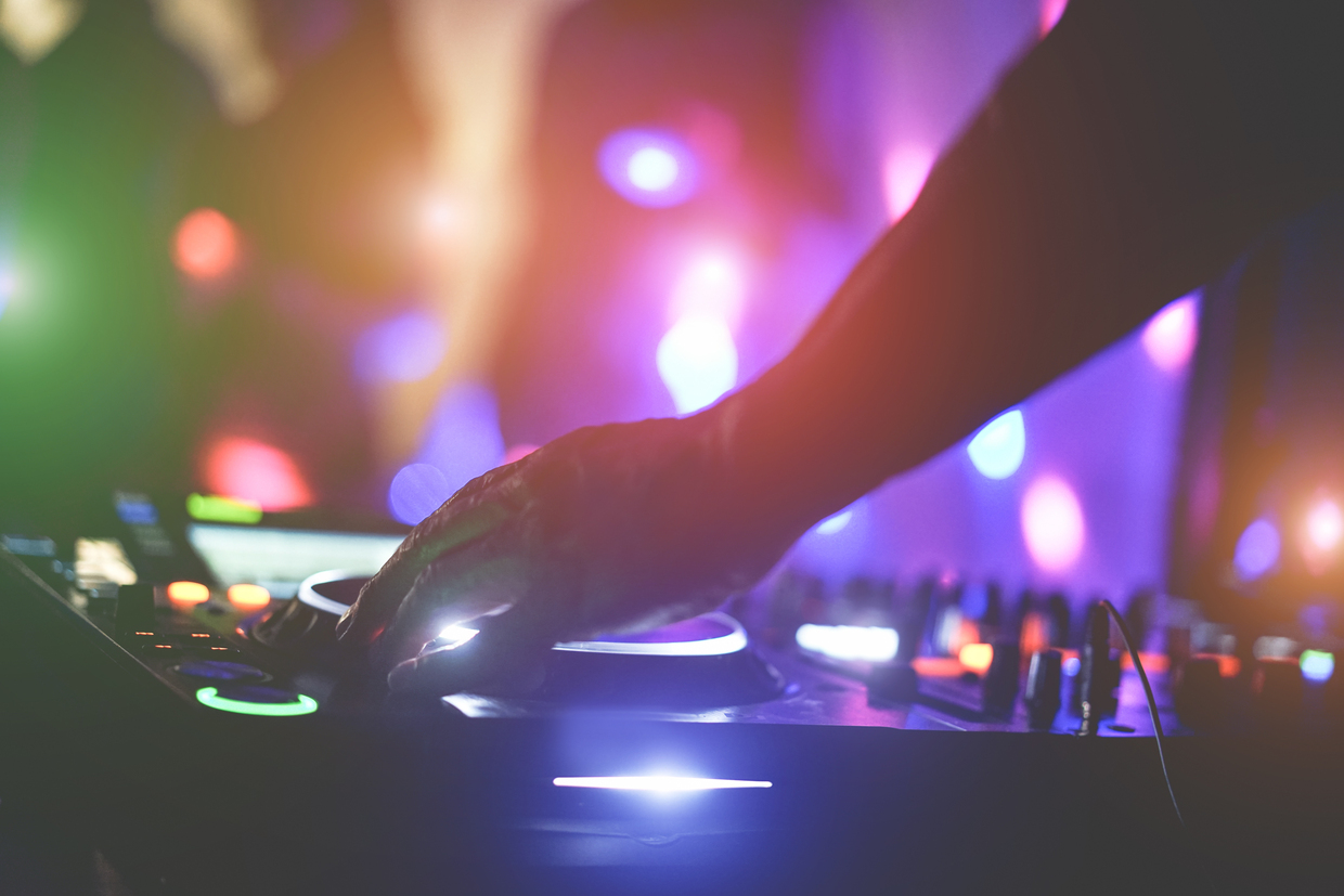 Dj mixing outdoor at beach party festival with crowd of people in background - Summer nightlife view of disco club outside - Soft focus on hand fingers - Fun ,youth,entertainment and fest concept